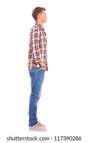 side view of a young casual man standing with his hand in his pockets, looking away from the camera