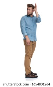 Side view of a young casual man making a funny face and gesture, standing on white studio background