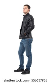 Side view of young casual man with hands in leather jacket pockets looking up serious. Full body length portrait isolated over white background.