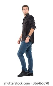 Side view of young casual man walking looking back over shoulder. Full body length portrait isolated over white background.