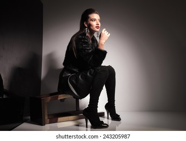 Side view of a young casual woman sitting on a stool, looking away from the camera.