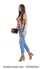 Side view of young casual woman wearing jeans holding purse walking. Full body length portrait isolated over white studio background.