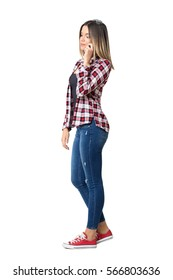 Side view of young casual woman talking on the mobile phone looking down. Full body length portrait isolated over white studio background.