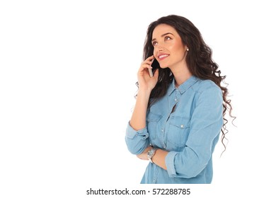 side view of a young casual woman speaking on the phone and looks away on white background