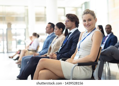 Side view of young Caucasian female executive sat in conference room, smiling to camera