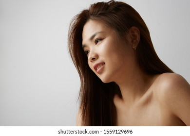 Side view of young Chinese woman posing on the white background. Isolated.