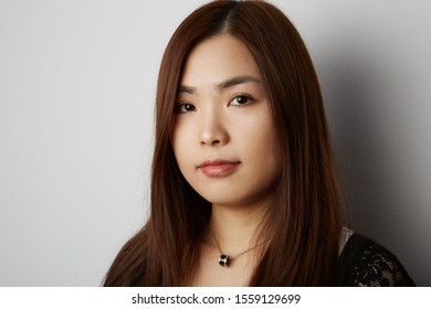 Side view of young Chinese woman with long hair posing on the white background. Isolated.