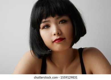 Side view of young Chinese woman with short hair posing on the white background. Isolated.