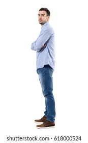 Side view of young confident businessman with crossed arms looking at camera. Full body length portrait isolated over white background.
