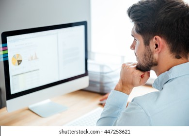 Side view of a young confident handsome businessman working on laptop in office