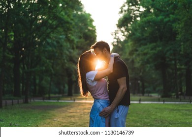 side view of young couple kissing each other on meadow with setting sun behind