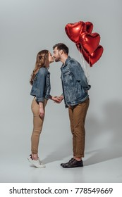 side view of young couple kissing while man holding red heart shaped balloons isolated on grey