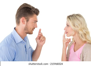 Side view of young couple looking at each other over white background