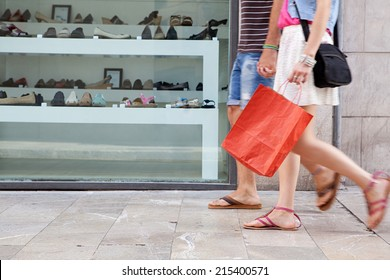 Side view of a young couple lower body section walking down a shopping street with a shoe store window display, carrying shopping bags and spending money on holiday. Consumer lifestyle, outdoors.