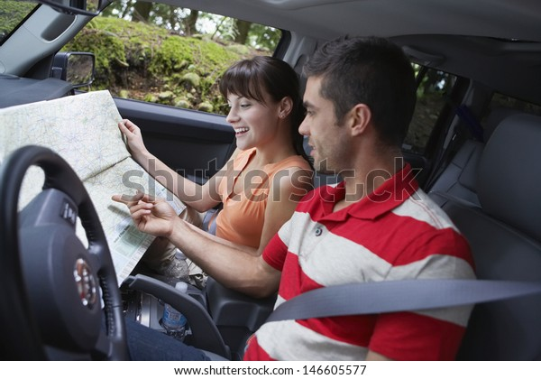 Side view of a young couple with map sitting in the car