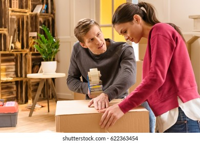 side view of young couple packing things for moving home