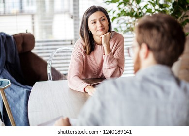 Side view of young co-workers talking at the table, woman working with laptop enjoying her coffee, man sitting opposite with documents, successful efficient workers.
