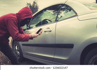 Side view of young criminal in black balaclava and hoodie holding smartphone and trying to interact with car by mobile application. Unknown person tries to get access to the vehicle using app. Fraud