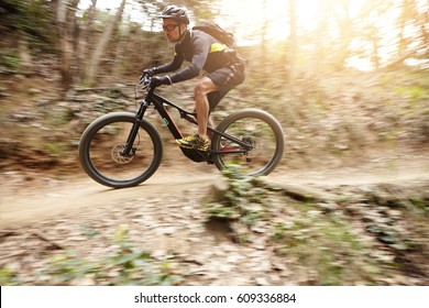Side view of young cyclist riding e-bike along trail in forest having concentrated expression on his face. Biker in helmet, glasses and sportswear speeding down on electric bicycle. Speed motion, blur