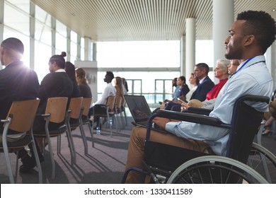 Side view of young disabled mixed race businessman using laptop during seminar in office building
