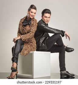 Side view of young fashion couple sitting on a white cube holding their legs crossed.