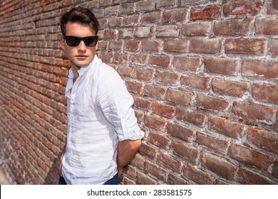 Side view of a young fashion man wearing sunglasses, leaning on a brick wall.
