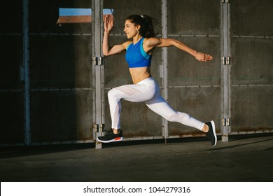 Side view of young female athlete running fast outside in the city. Sporty woman training.