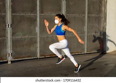 Seitliche Sicht auf junge weibliche Athleten, die schnell draußen laufen und Gesichtsmaske in der Stadt tragen. Sportliche Frauen-Training mit Schutz gegen Coronavirus.