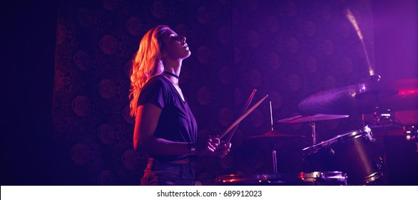 Side view of young female drummer performing in illuminated nightclub