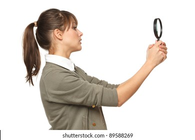 Side view of young female looking with magnifying glass, over white background