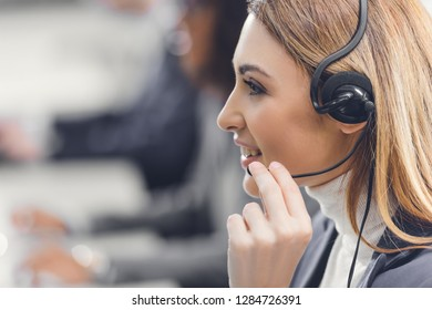 side view of young female teleworker in headset smiling and working in office