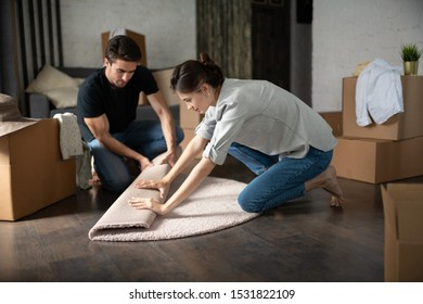 Side view of young female unrolling soft carpet with assistance of boyfriend while moving into new apartment together