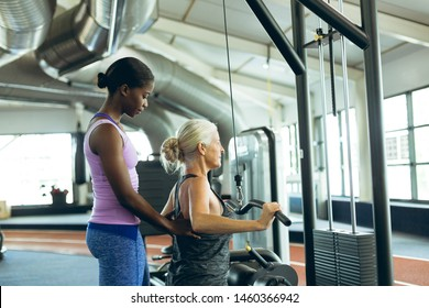 Side view of young fit African-american female trainer assisting active senior Caucasian  woman on lat pulldown machine in fitness studio. Bright modern gym with fit healthy people working out and