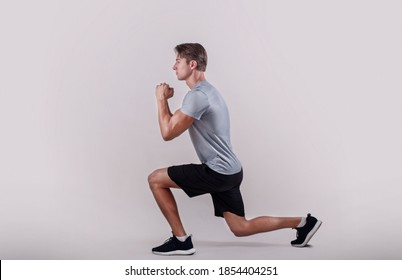 Side view of young fit guy in sportswear doing lunge on light studio background. Professional millennial bodybuilder warming out before strength training, doing aerobic exercises