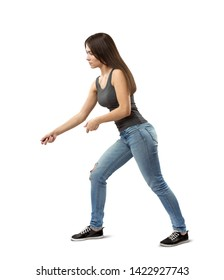 Side view of young fit woman in gray top and blue jeans bending forward slightly and posing as if holding invisible rope isolated on white background. Household chores. Train your body. Keep fit.