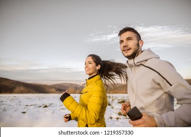 Side view of a young fitness couple running in nature in winter.