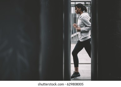 Side view of young fitness woman in sportswear jogging on stadium