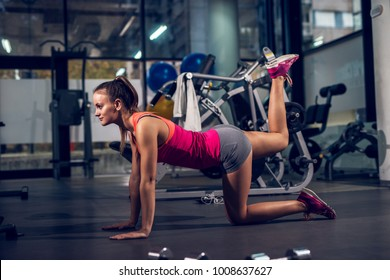 Side view of young focused satisfied attractive healthy sporty active shape girl doing legs exercises and warming while kneeling on the floor and raising one leg up in the gym.