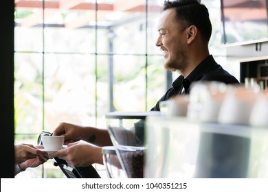 Side view of a young friendly bartender serving a short espresso to a customer in a modern coffee shop