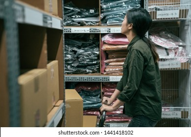 side view young girl worker searching products in warehouse of company. woman staff pushing cart walking in stockroom. female employee wearing uniform prepare parcel for customer in storehouse.