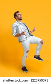Side view of young guy in stylish outfit gesturing and screaming while standing on bright yellow background and celebrating success