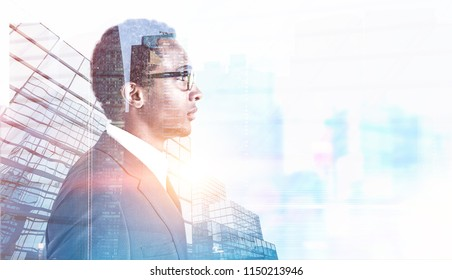 Side view of a young handsome African American businessman wearing glasses and a gray suit. A morning city background. Toned image double exposure mock up