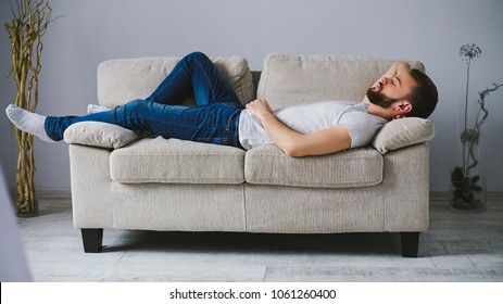 Side view of a young handsome bearded man in casual clothes sleeps on the couch in a room at home.