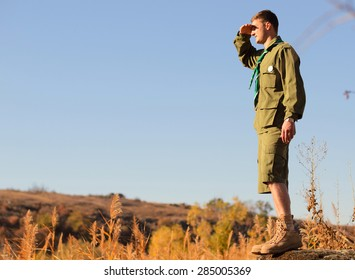 Side View of a Young Handsome Boy Scout Standing on the Rock and Watching Over the Wide Field