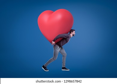 A side view of a young handsome man in a casual outfit carrying a huge red heart on his back. Love affair. Cardiology centre. Help people.