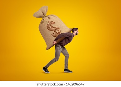Side view of young handsome man in casual clothes carrying huge heavy sack with dollar symbol on. Avidity incarnate. Earn money. Become rich.