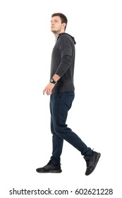 Side view of young handsome sporty man in sweatshirt and sweat pants walking looking up. Full body length portrait over white studio background.
