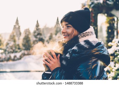 Side view of young happy smiling woman standing in open air in cold weather admiring nature and holding paper cup with beverage