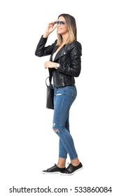 Side view of young happy stylish woman in jeans touching sunglasses looking away.  Full body length standing portrait isolated over white background.