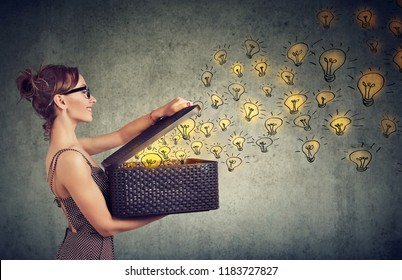 Side view of young happy woman holding a box with brilliant ideas spreading knowledge
